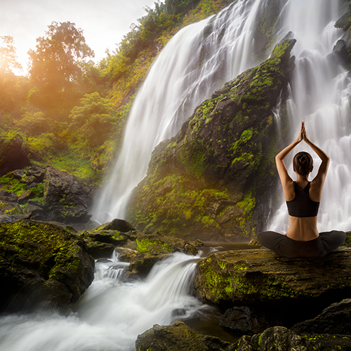 A person meditating near a waterfall